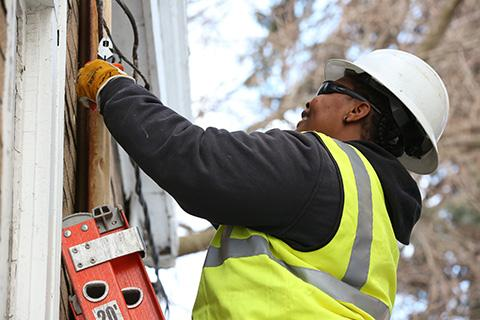 Meter Installer Apprentice Sarina Scott secures an electrical line to a property.